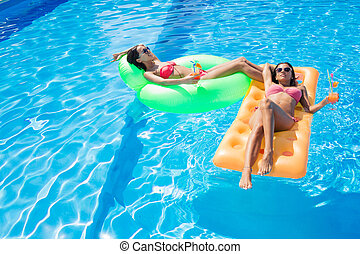 Girls resting on air mattress in swimming pool