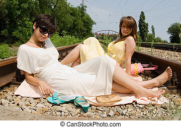 Girls resting on the railroad carelessly