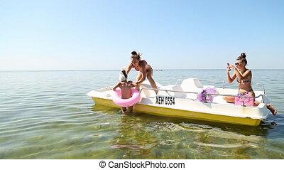 Girls ride on a catamaran on the sea