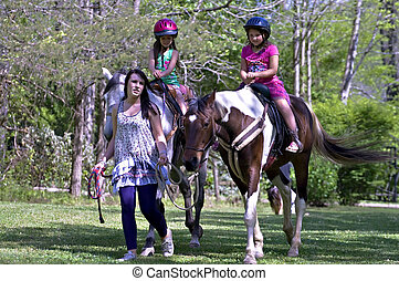 Girls Riding Horses - A teenage girl leading a horse with...