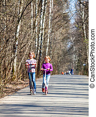 Girls riding kick scooters - Two little girls riding push...