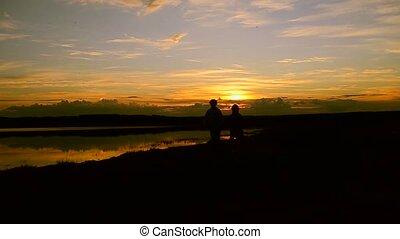 Girls running along the beach at sunset background