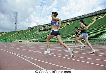 girls running on athletics race track - three athlete woman ...