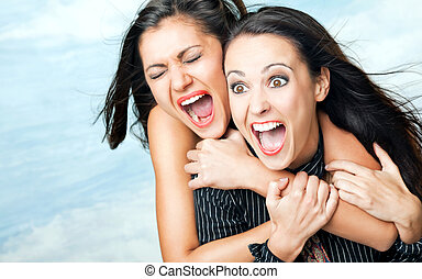 Two beautiful girls hugging and screaming with excitement