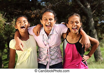 Three young school girl friends share a hilarious moment together while in the park in the sunshine