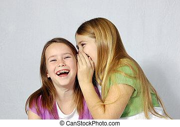 Two girls sharing a secret joke