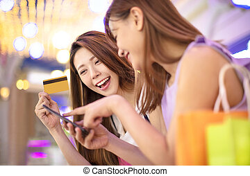 girls showing credit card and watching phone in the shopping mall