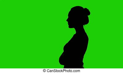 Girl's silhouette in profile with arms crossed on green background