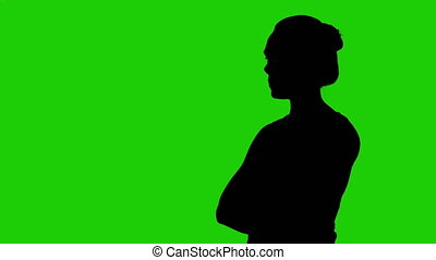 Girl's silhouette with arms crossed on green background