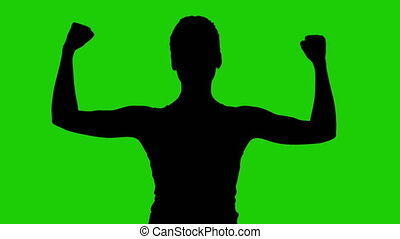 Girl's silhouette with hands up on green background