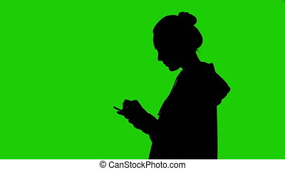 Girl's silhouette with smartphone on green background
