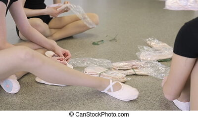 Girls sit on floor in dancing class elegantly stretching their legs.
