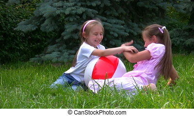 girls sits with ball on grass in park and plays