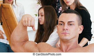 Girls sitting behind an easel draws a muscular shirtless guy...