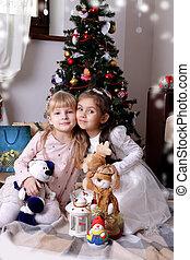 Girls sitting cheek to cheek under Christmas tree