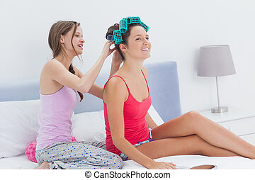 Girls sitting in bed one wearing hair rollers