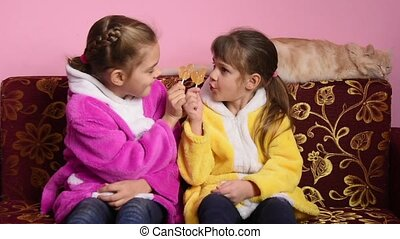 Girls sitting on the couch and having fun lick lollipops...