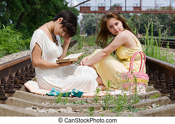 Girls sitting on the railroad carelessly