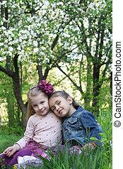 Girls sitting under spring tree