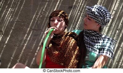 Girls smoke a hookah in the shadow of a Bedouin house.