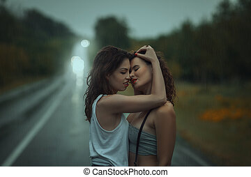 Girls stand having embraced on street in the rain. - Girls...
