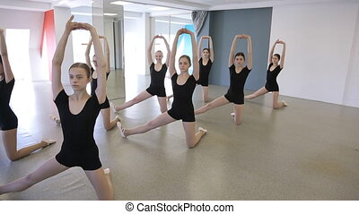 Girls stand in pose and do stretching exercise in dancing class