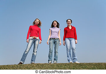girls stand on meadow