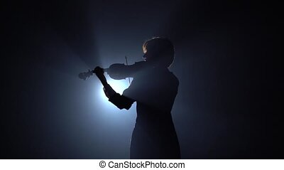 Girls standing back and playing on violins in a dark room....