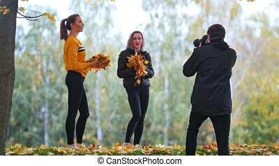 Girls stay near the cameraman holding leaves. Girls throwing...