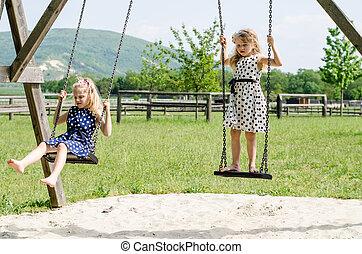girls swinging - little blond girl swinging outdoor