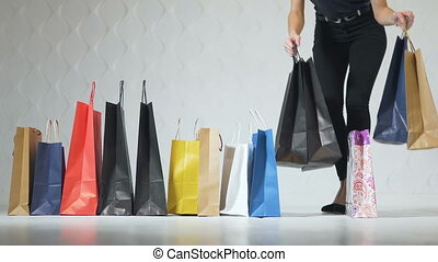 Low shot of attractive girls taking shopping bags in turn while walking