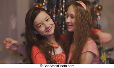 Girls teens hugging smiling on the background of Christmas tree