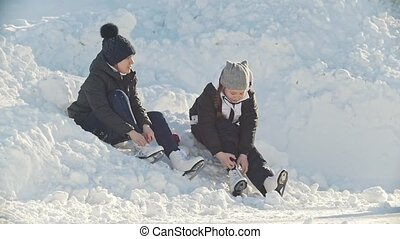 Girls Teens wearing skates sitting in a snowdrift near the...