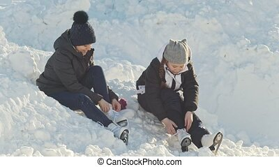 Girls Teens wearing skates sitting in a snowdrift near the...
