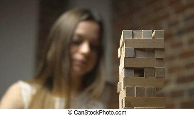 Girl's Turn in Jenga Game - Jenga game, caucasian dark hair...