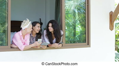 Girls Use Cell Smart Phones Talking Standing At Window Sill Laugh Outside View, Morning Young Women Group Communication