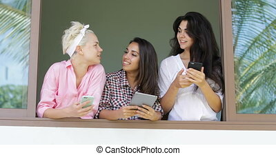 Girls Use Cell Smart Phones Talking Standing At Window Sill Outside View, Morning Young Women Group Communication
