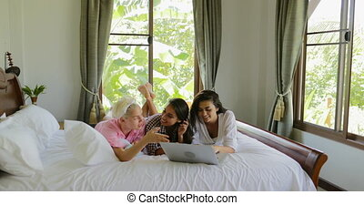 Girls Using Laptop Computer Lying On Bed Laugh Talking,...