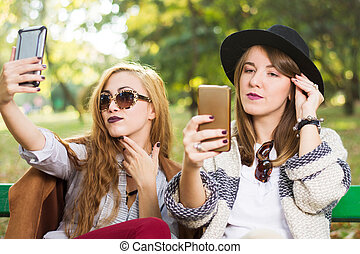 Girls using phones on a bench