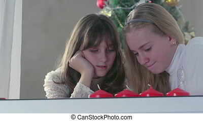 Girls using smart phone near Christmas tree at home