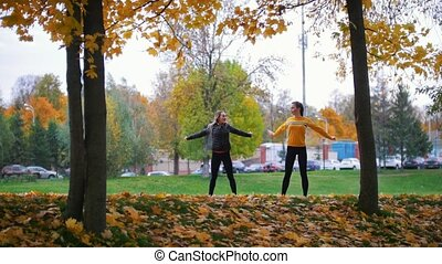 Girls warming up and doing gymnastics in the autumn park....