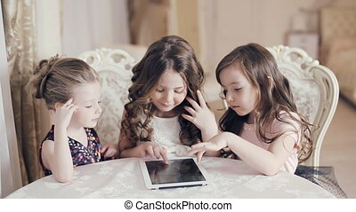 Girls watching photos on tablet and wonder