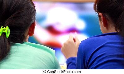 Girls watching tennis sport on TV
