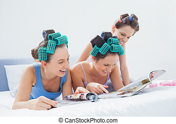 Girls wearing pajamas and hair rollers sitting in bed with magazines