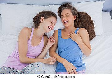 Girls wearing pajamas lying in bed and laughing at slumber...