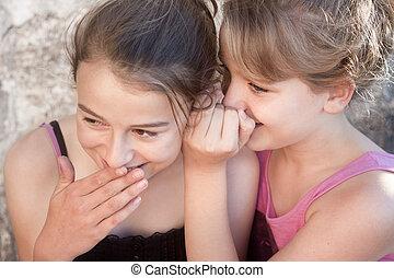 Girls whispering secrets