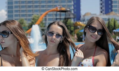 Girls with a beautiful figure in swimsuit and sunglasses smiling
