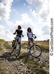 Girls with a bicycle enjoying