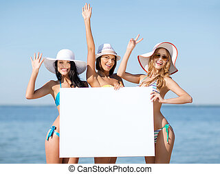 girls with blank board on the beach - summer holidays and...