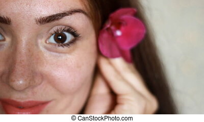Girls with freckles on face and orchid flower in hand...